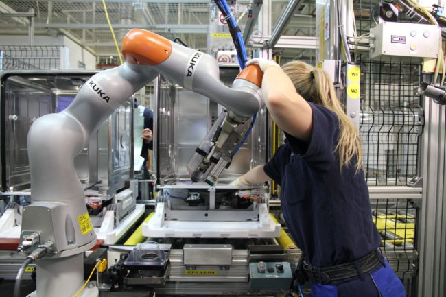 robots KUKA collaborating with workers